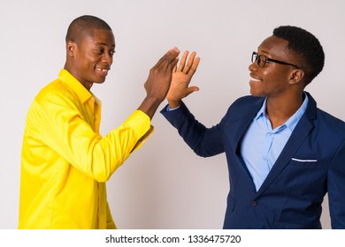 Two young happy African businessmen giving high five together