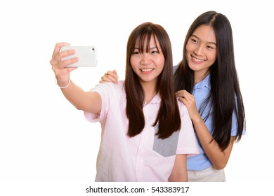 Two young happy Asian teenage girls smiling and taking selfie with smart phone