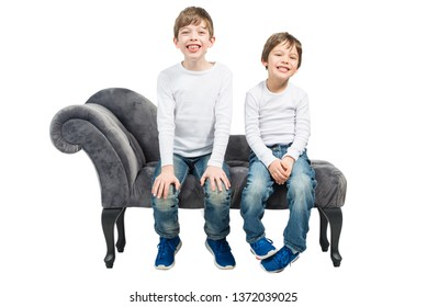 Two young happy boys sitting on sofa, isolated on white background