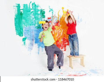 two young happy children - boy and girl - painting white wall