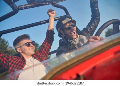 two young happy excited men enjoying beautiful sunny day while driving a off road buggy car