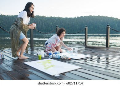 Two young happy fashion women painting a picture on an easel on a warm sunny day at nature. Art therapy, relax and hobby concept