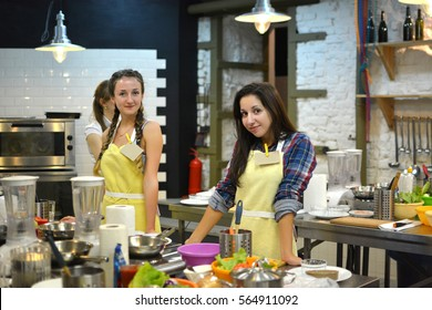 Two young happy female friends cooking and talking in the kitchen. Cooking class/Two young happy female friends cooking and talking in the kitchen. Cooking class