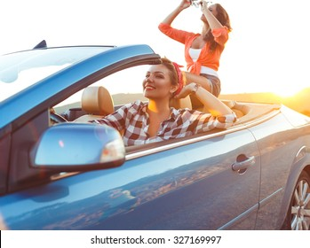 Two young happy girls driving a cabriolet