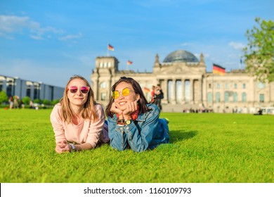 Two Young happy girls wearing sun glasses lying on a grass and have fun in front of the Bundestag building in Berlin. Studying abroad and travel in Germany concept