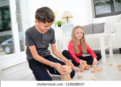 two young happy kids brother and sister together having fun at home with a wooden brick toy game