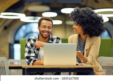 Two young happy multiracial business people sitting at the desk in the modern office, using laptop and discussing project, man and woman working together in coworking space