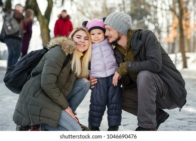 Two young happy parents pose with their charming little daughter in winter park