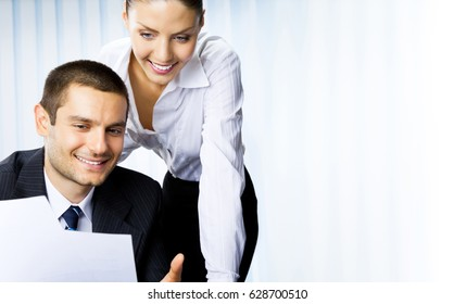 Two young happy smiling successful businesspeople working with document or contract at office. Success in business and teamwork concept.