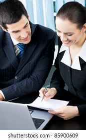 Two young happy smiling successful businesspeople signing document or contract at office