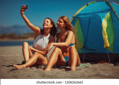Two young happy woman camping on the beach during the summer