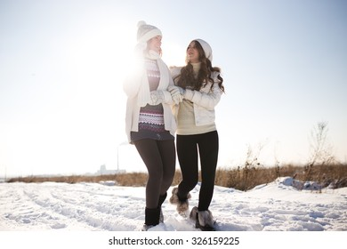 Two young happy woman, two friends, having fun in bright winter day. Lifestyle concept