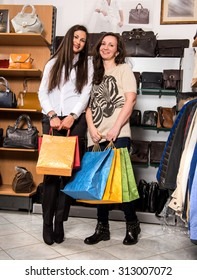 Two young happy woman with shopping bags in the mall