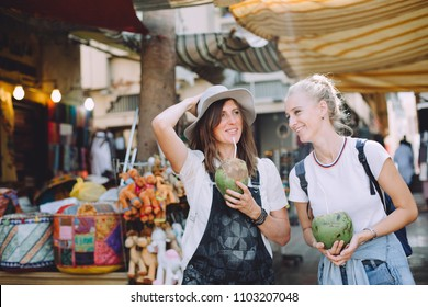 Two young happy women with coconuts at traditional bazaar in Dubai, UAE