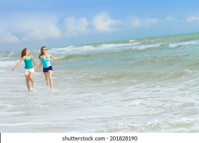 two young happy women enjoying life outdoors on sea background