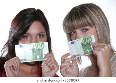 Two young happy women holding money