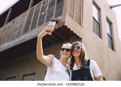 Two young happy women taking selfie at old street in Dubai, UAE