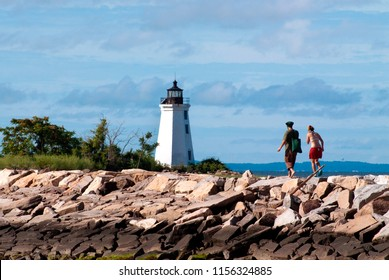 Two young hikers walking along jetty towards Black Rock Harbor lighthouse in Bridgeport, Connecticut. It is a popular park enjoyed by many visitors in the summer season.