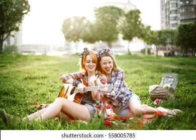 Two young hipster girls having fun on the picnic in a summer park
