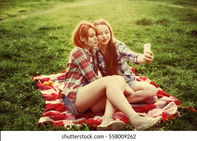 Two young hipster girls having fun on the picnic, making selfie on a smartphone