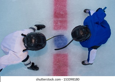Two young hockey players stands on red line in face off. Top view
