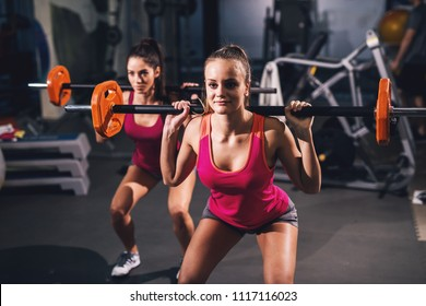 Two young hot girls are doing situps with orange weights on their shoulders in a dark gym.