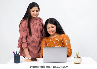 Two young Indian girls working infront of a laptop, Two teenagers smile as they chat on a computer.