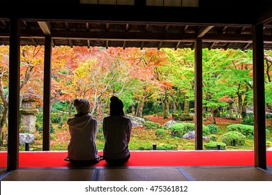 Two young Japanese girls sit on red carpet floor to see and enjoy Autumn colorful foliage Japanese garden at Enkoji temple, Kyoto, Japan. Here is Rinzai Zen Sect and very famous during fall season.