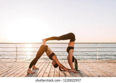 Two young ladies in black sporty tops and leggings standing and training yoga poses by the sea. Pretty women practicing yoga together with beautiful sea view on background