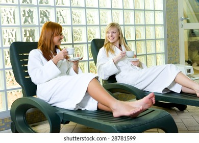 Two young ladies clothed bathrobe sitting on deckchairs. They're talking and drinking coffee.