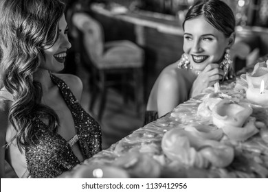 Two young laughing stylish girls dressed classical style in interior of luxury club.