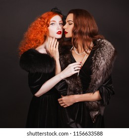 Two young lesbian woman with curly long hair in black dress touch each other on dark background. Pale skin and red lips. Lesbian fetish couple in studio. Fabulous vintage models. Soft touch