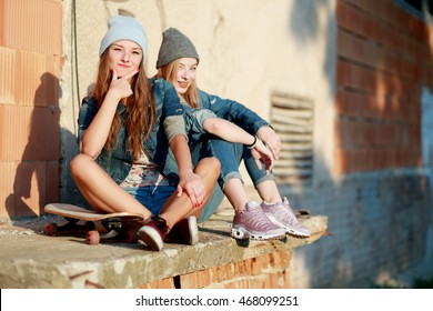 Two young longboarding girl friends sitting together on long-board and having fun. Outdoors