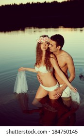 Two young lovers in a lake at night. Girl and man at sunset in the lake.