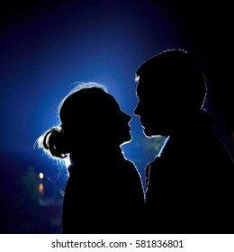 Two young lovers look each other in backlight, blue light