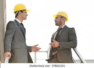 Two young male architect discussing on stairway