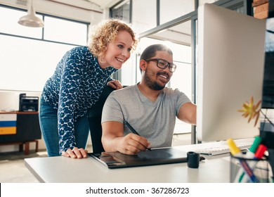 Two young male and female designers working together, with man editing artwork using graphics tablet and a stylus. Creative people coworking on a new project in office.