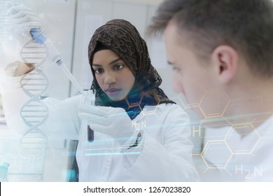 Two young male and female multiethnic, mixed race students  scientists doing experiments in laboratory.