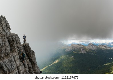 two young male mountain climbers on very exposed Via Ferrata in the Dolomites of Italy