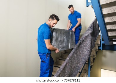 Two Young Male Movers In Uniform Carrying Furniture On Staircase