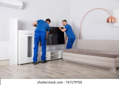 Two Young Male Movers In Uniform Placing Television In Living Room