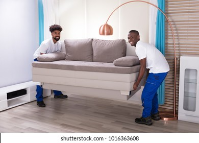 Two Young Male Movers In The White Uniform Placing The Sofa In The Living Room
