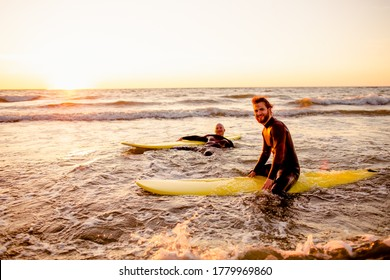 Two young male surfers in black wetsuits with longboards in a water at sunset ocean. Water sport adventure camp and extreme swim on summer vacation.
