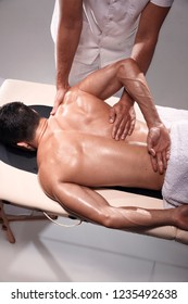 two young man, 20-29 years old, sports chiropractor indoors in studio, photo shoot. Chiropractor pushing muscular mans back with his hands.