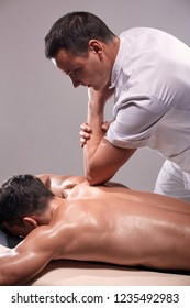 two young man, 20-29 years old, sports physiotherapy indoors in studio, photo shoot. Physiotherapist massaging muscular patient back with his elbow.