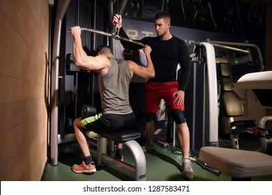 Two young man, 20-29 years. One man exercising back muscles, training on lat pulldown machine, while other friend or coach is helping him. In gym, with professional fitness equipment.
