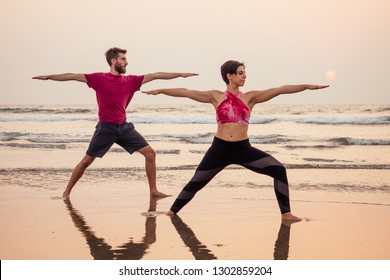 two young man and beautiful woman on beach doing fitness yoga exercise together. Acroyoga element for strength and balance at sea octan goa india sunset