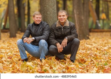 two young man in black jacket in autumn park, crouched near tree, smiling