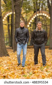 two young man in black jacket in autumn park walking on yellow foliage