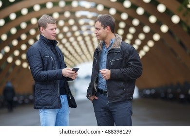 two young man in black jacket on background of lights installation main park alley, looking at each other